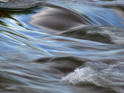 Flowing water with the reflection of the blue sky taken with a slow shutter speed